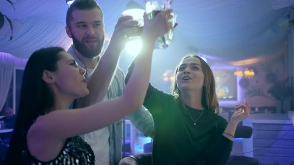 Cover Image for Attractive Friends Have Fun at Party and Make a Toast with Glasses in Their Hands