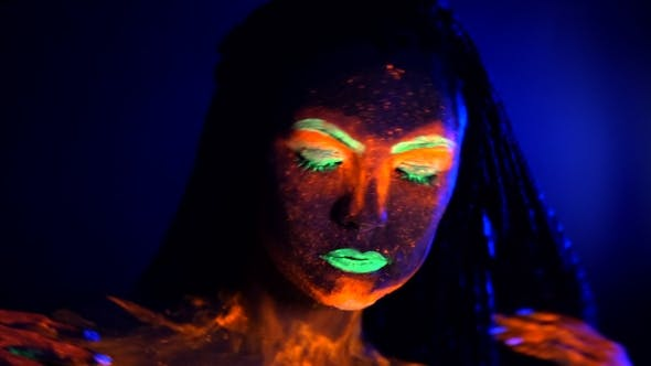 Thumbnail for Fashion Sexy Dancer with Braids in Neon Light. Fluorescent Makeup Glowing Under Ultraviolet Light