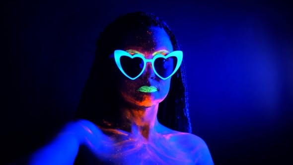 Thumbnail for Fashion Sexy Dancer with Heart Shaped Glasses in Neon Light. Fluorescent Makeup Glowing Under