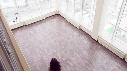 a Woman in a Red Dress Barefoot Walks Along the Big Penthouse Room To the Window. She Is Spinning