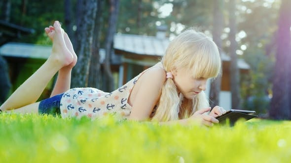 Thumbnail for Carefree Blonde Girl Is Playing on the Tablet. Lies on the Green Grass Near the House, the Sun