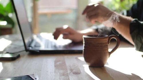 A man works at home in front of a laptop monitor and drinks hot tea. Focus on a mug of tea.