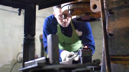 Making the Knife Out of Metal at the Forge. Man Using Pneumatic Hammer To Shape Hot Metal.