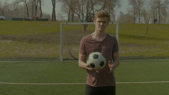 Portrait of Smiling Teenager Holding Soccer Ball