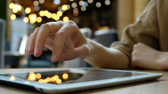 Thumbnail for Woman Uses a Tablet Computer Pc on a Blurry Background in Cafe,