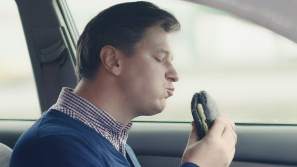Thumbnail for A Man Is Eating a Hamburger in the Car. Fast Food.