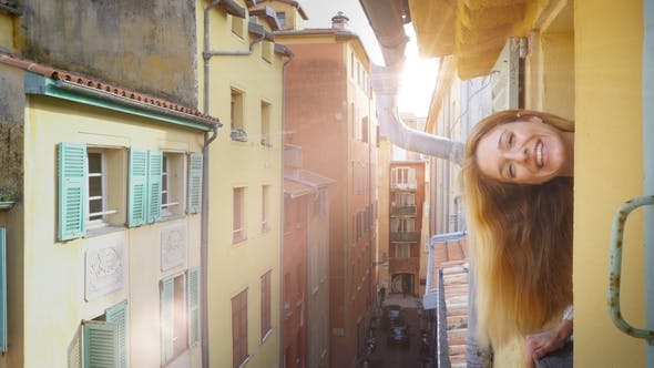 Thumbnail for A Young Woman Looking Out of the Window To a Medieval Street Smiling and Waving Her Hand