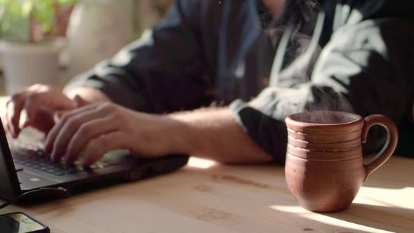 Thumbnail for of Tea Cup and Laptop on the Table in Cafe. Cup Is Full of Brown Hot Beverage, Which Is Waving. A