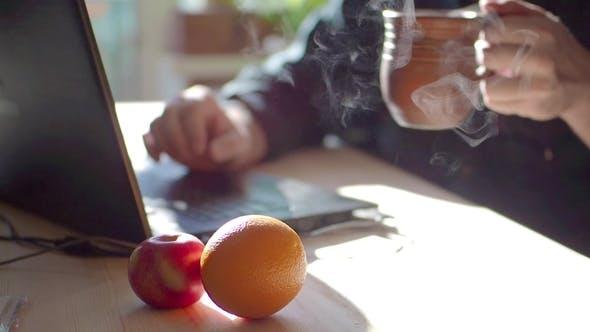 Männlich im Café mit Laptop. Konzentrieren Sie sich auf die Tasse heißen Tee.