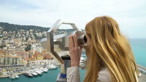 Young Woman Watching Through the Stationary Binoculars at a Scenic Overlook in Nice, France