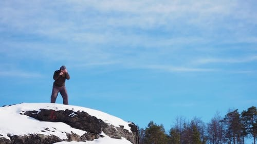 A boxer trains on the top of a mountain. He prepares for battle and trains under extreme conditions.