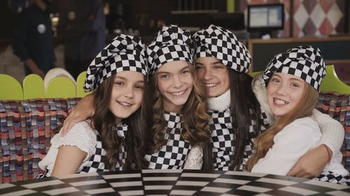Portrait of Four Funny Girls Looks at Camera in Embraces in Pizzeria