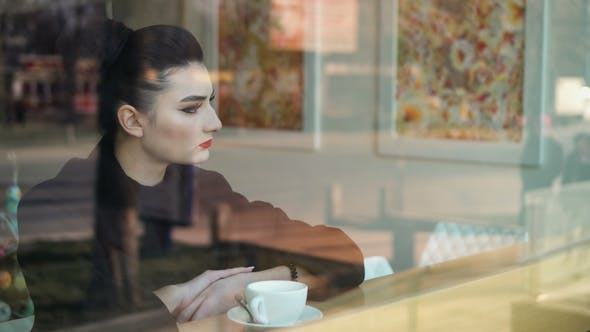 Thumbnail for Young Miserable Looking Woman Sits on Windowsill and Slowly Drinks Coffee