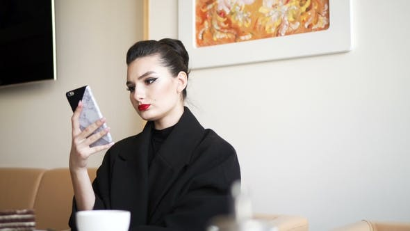 Thumbnail for Young Girl in the Restaurant. Business Woman Uses the Smartphone