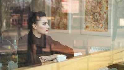 Melancholy Time. Young Miserable Looking Woman Sits on Windowsill and Slowly Drinks Coffee