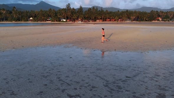 Thumbnail for Young Woman Jogging at the Beach on Sunset