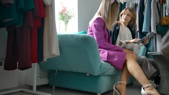 Young Woman Discussing Online Catalog with Friend