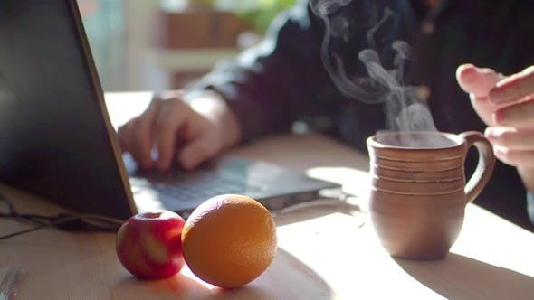 Thumbnail for A Man Is Working on a Laptop. He Drinks Hot Tea. On the Cliff Lie the Apple and Orange. Healthy