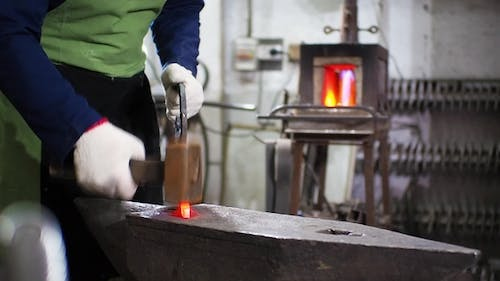 Slide Shot of Blacksmith Who Shapes Hot Steal with a Hammer