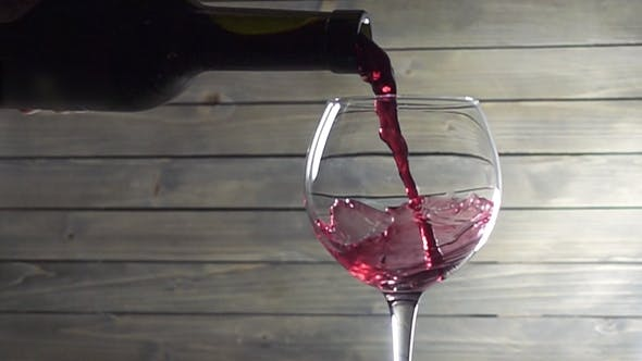 Thumbnail for Pouring Red Wine Into the Glass Against Wooden Background.
