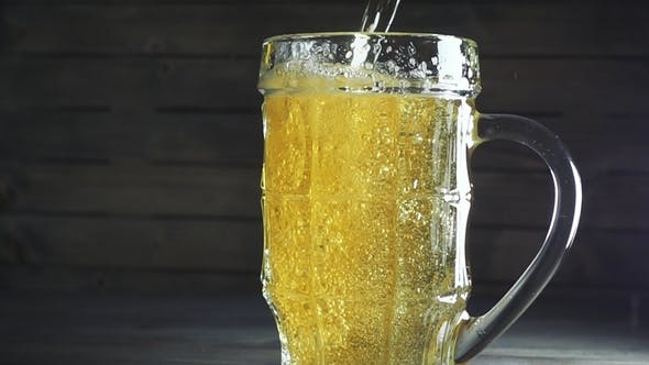 Thumbnail for Shot of Pouring Beer Into Beer Mug. Over Dark Wooden Background