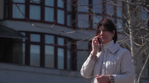 Thumbnail for Senior Woman Talks on Phone at the Office Building Background