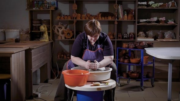 Thumbnail for an Adult Woman Is Engaged in Creating a Vase of Clay, She Sits Behind a Potter's Wheel and Forms