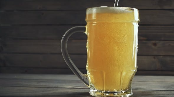 Thumbnail for Shot of Pouring Beer Into Beer Mug. Over Wooden Background