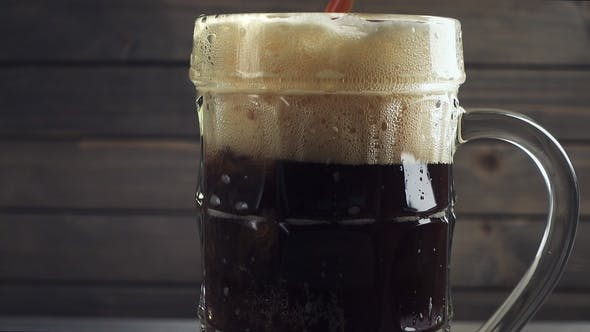 Thumbnail for Gießen kaltes dunkles Bier in Bierbecher. Über dunklem Holzhintergrund.