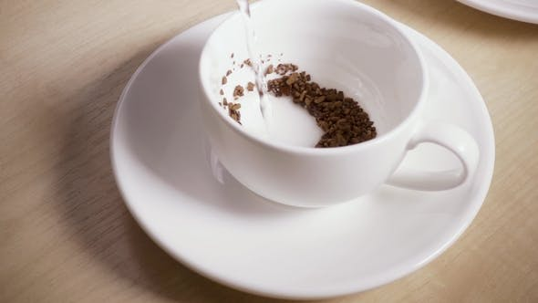 Water Is Poured Into a Mug with Instant Coffee