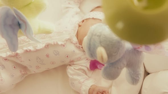 Thumbnail for Baby Girl Looking at Defocused Toy Mobile in Her Cot
