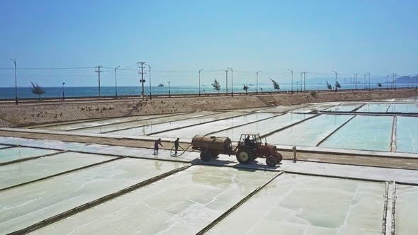 People Work on Salt Fields Pouring Water from Tank