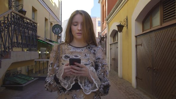 Thumbnail for Young Girl Walking Down the Street with a Phone in Hands