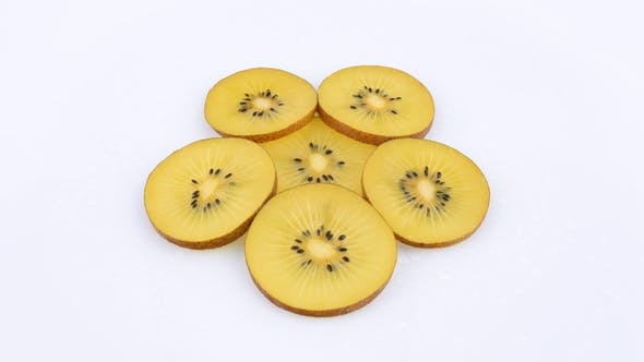 Thumbnail for Slices of Golden Kiwi Rotating on a Turn Table. Isolated on White Background.  .