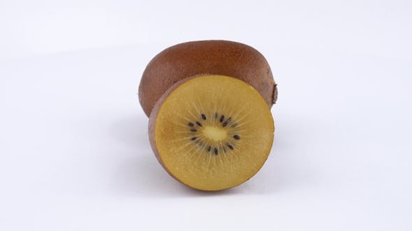 Thumbnail for One and a Half of Golden Kiwifruit Rotates on a Turn Table. Isolated on White Background.