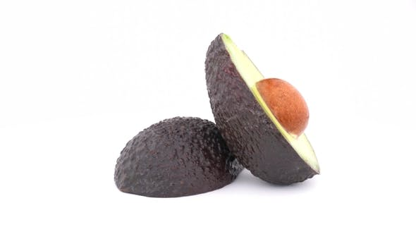 Thumbnail for Two Parts of Sliced Avocado Haas Slowly Rotates on Turn Table. Isolated on White Background.