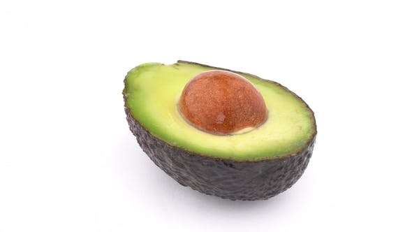 Thumbnail for Sliced Raw Avocado Haas with a Seed Slowly Rotates on Turn Table. Isolated on White Background.