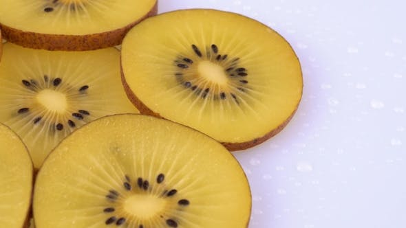 Thumbnail for Extreme  of Golden Kiwi Slices Rotating on a Turntable. Isolated on White Background. .