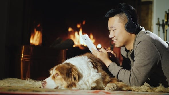 Thumbnail for A Happy Asian Man Lies By the Fireplace with a Dog. Uses a Digital Tablet