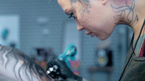 Woman, a Tattoo Artist, Does a Tattoo in the Salon.