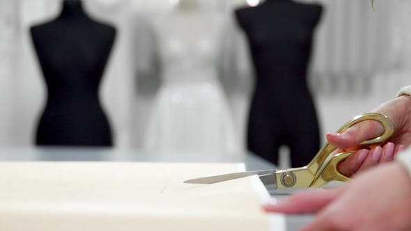 Thumbnail for Beautiful Fashion Designer Girl Cuts out Paper Patterns for Fabric with Gold Scissors