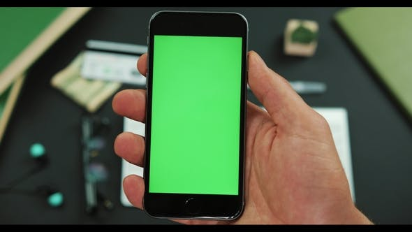 Thumbnail for Man Holds a Black Smartphone with Green Screen Over a Working Table