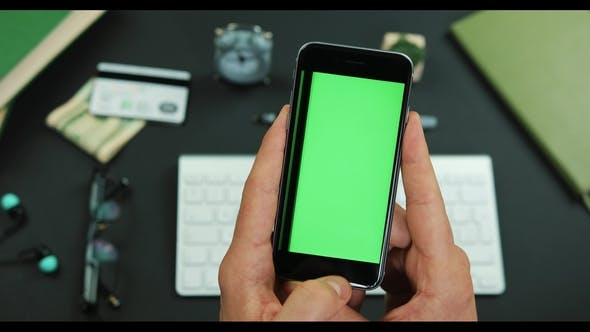Thumbnail for Man Holds Smartphone with Green Screen Over a Working Table and Scrolls Something on It