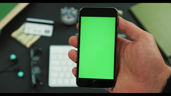 Thumbnail for Man Holds Smartphone with Green Screen Over a Working Table