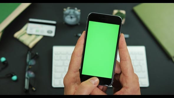 Thumbnail for Man Holds Smartphone with Green Screen Over a Working Table and Taps Something on It