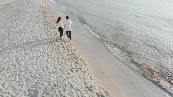 Thumbnail for Aerial Drone View Above Couple in Love Walking on Sandy Sea Beach. Pair Are in Love, Having Good