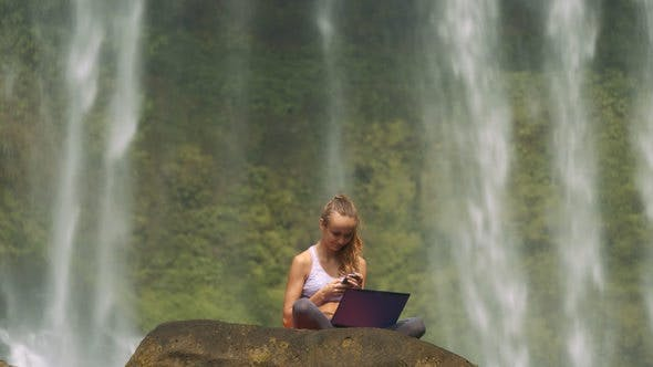 Girl Sits with Laptop and Phone on Cliff at Water