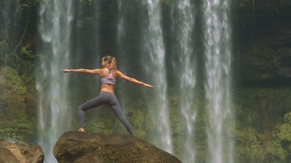 Thumbnail for Slim Girl Poses on Round Rock against Waterfall