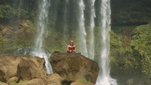 Thumbnail for Lady Reads Diary on Rock among Waterfall Streams