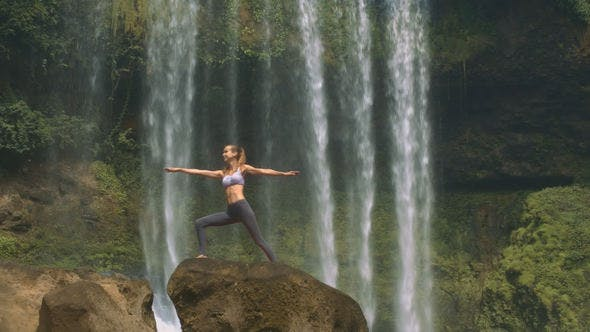 Thumbnail for Girl Stands in Yoga Pose on Brown Rock at Waterfall